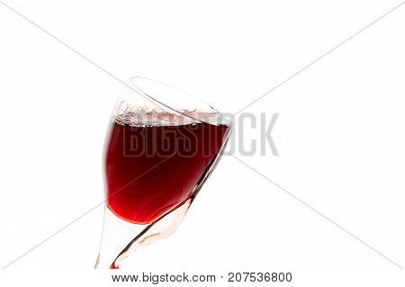 a glass of red wine on white background isolated in backlight