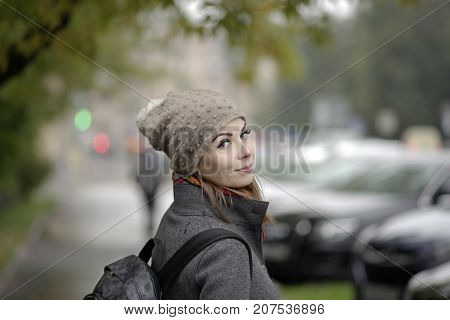 Young woman with a happy face posing in a rainy day the traffic lights in the blurred background