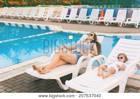 Endless summer. Cute baby and mother relaxing at sunbed near pool at resort. A little girl wearing sunglasses. Child and mom sunbathe. Fashion girls, friends, family at resort