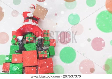 Santa sitting at the top of many big gift boxes and reading wish list. Black Friday 2017 at United States. Wishes. Copy space at white background. Cristmas shopping. Xmas, New Year Merry Christmas