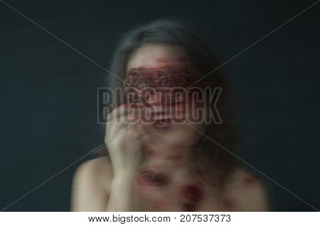 portrait of a girl with realistic ulcers and worms crawling out of her eyes. creative halloween makeup. Blurred photo.