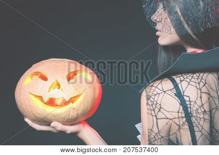 Entrance is limited to nightclub, dress code. Fashion young woman with pumpkin going to Halloween party 2017. Beautiful woman like witch. Moon, scary cemetery. Hallowen costumes, pumpcin