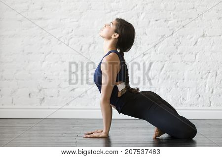 Young woman practicing yoga, stretching in upward facing dog with padmasana legs exercise, Urdhva mukha shvanasana pose, working out, wearing sportswear, black top, pants, indoor full length, studio