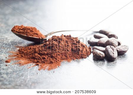 Tasty cocoa powder and cocoa beans on old kitchen table.