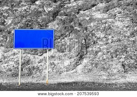 An image of blue empty street sign with stone wall background clipping path.