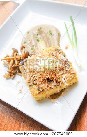 fried tofu steak and mushroom on plate