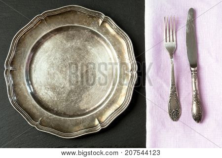 Vintage metal dish with silverware on slate background with copy space for your menu or recipe. Table place setting. Top view.