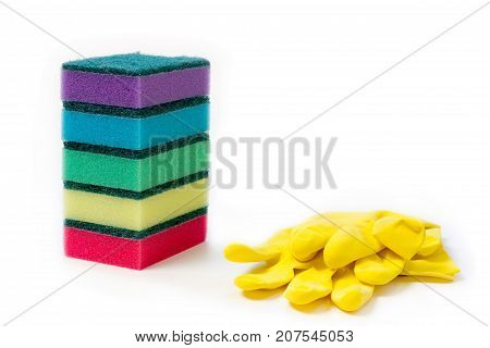 pile of colorful sponge and yellow rubber gloves for wet cleaning and washing dishes on white background with space for text
