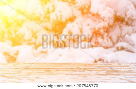 winter blurred natural background in the sunlight with a wooden table and a mounting area for the placement of objects. mock up for text congratulations phrases lettering