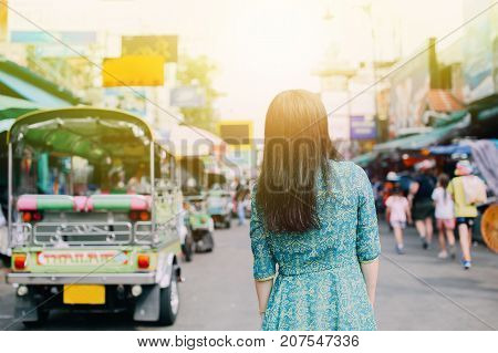 Woman in traditional Asian dress on Khaosan road with tuk tuk taxi behind appreciating Thai local culture - travel and local life concept
