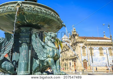 Close up of fountain of Lions, 19th century fountain in Parada Leitao Square in historic city of Porto in Portugal. The beautiful Carmo church on blurred background.
