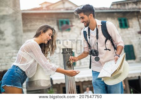 Young couple of tourist near a drinking fountain with water