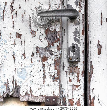 Piece of old door peeling white paint broken door old door handle.