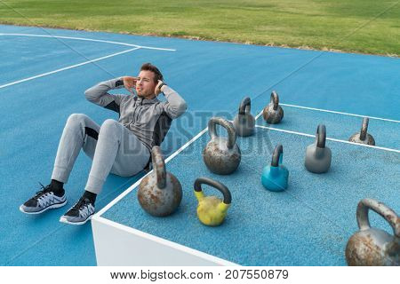 Fitness gym man training abs doing situps exercise crunches for weight loss and ab muscles toning. Male athlete doing core workout exercises.