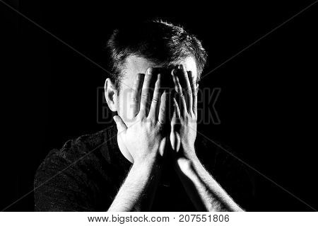 Low-key portrait of stressed young man with hands on a face lonely sad negative