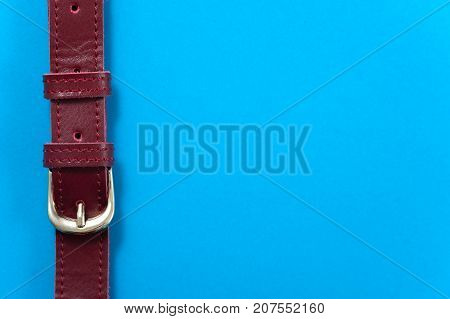 Detail Leather bag on blue background, closeup. Buckle strap bag texture firmware. Copyspace
