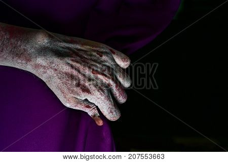 closeup of the scary hand of an undead man drawing a purple stage curtain, with a blank black background in the background
