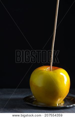 One caramel apple on a small tin plate vertical