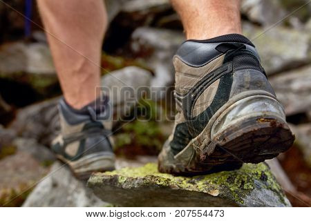 Hiking man with trekking boots on the trail. Closeup