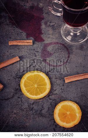 Spilled red mulled wine and cinnamon over dark background, retro toned