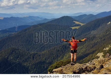 Hiker with backpack standing on top of a mountain with raised hands and enjoying sunrise