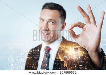 Successful everywhere. Experienced manager showing finger circle while feeling excited