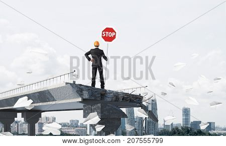 Rear view of engineer in helmet holding stop sign while standing among flying paper planes on broken bridge with cityscape on background. 3D rendering.