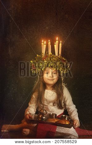 Little caucasian girl in Saint Lucia costume with crown of candles and traditional swedish sweet. Copy space.