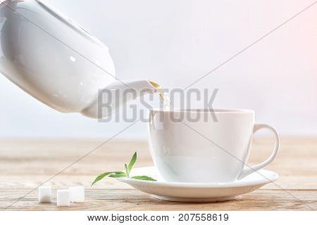 Pouring green tea from white ceramic teapot into a matching tea cup