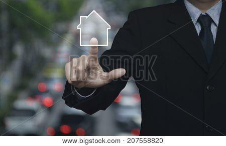 Businessman pressing house icon with copy space over blur of rush hour with cars and road street and expressway Real estate concept