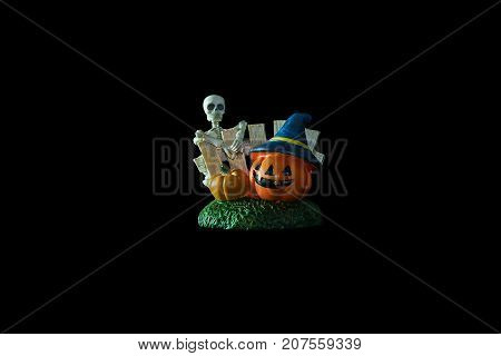 Halloween concept : Low key image of Plastic human skeleton model and ceramic pumpkins isolated on black background