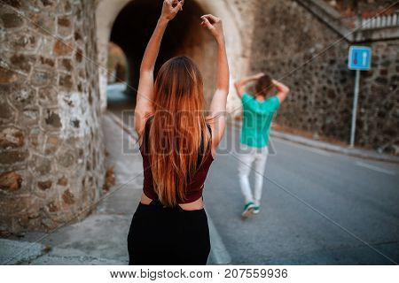 Red hair woman walking towards a tunnel with raised arms. Man walking before her on the road.