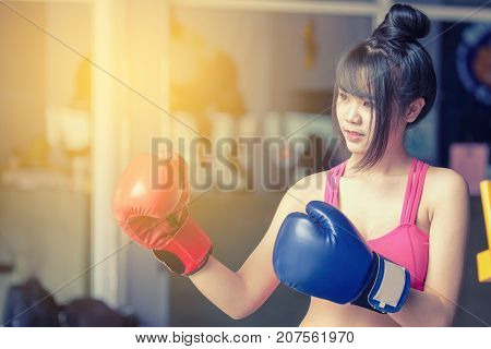 Attractive Female Punching A Bag With Boxing Gloves