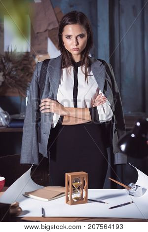 Architect woman working on drawing table in office or home. Studio shot with hourglass. concept of lack of time