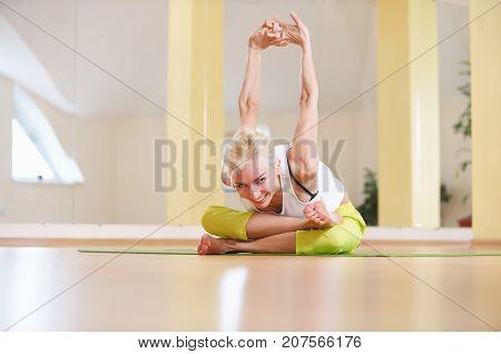 Beautiful sporty fit yogi woman practices yoga asana Adho Mukha Agni Stambhasana in the yoga class