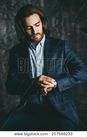 Time concept. Good looking handsome man looks at his wristwatch. Fashion shot.
