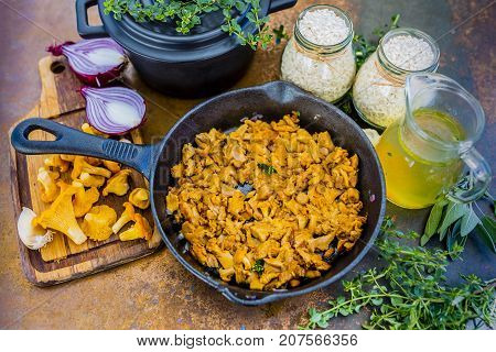 Chanterelle mushrooms with herbs on a frying pan.