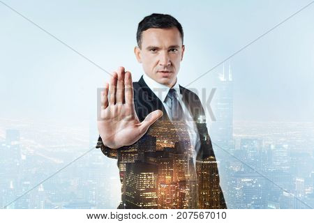 Stop please. Confident serious manager showing his palm to you while being slightly hostile