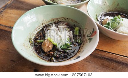 Boat noodles beef super spicy Thai food has meatballs and morning glory The soup is dark soy sauce with blood.
