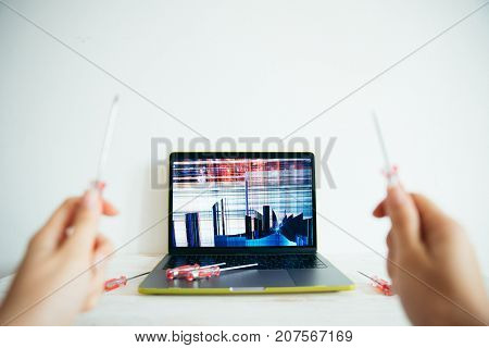 screwdriver in hands with broken laptop on background concept