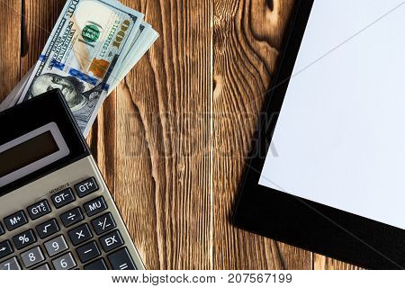 paper plate, money and black calculator on wood table wit copy space