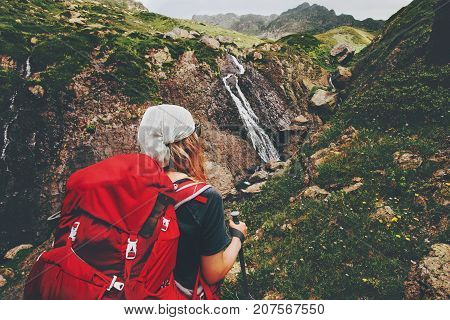Woman backpacker hiking enjoying waterfall view in mountains Travel Lifestyle adventure wanderlust concept summer vacations active outdoor