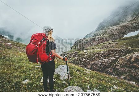 Woman backpacker hiking in foggy mountains Travel Lifestyle adventure wanderlust concept summer vacations active outdoor