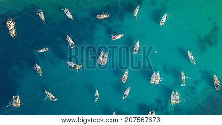 Aerial view of group of sailing boats anchoring on buoys. Bird eye view, water sport theme.
