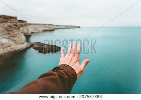 Hand touching cold sea landscape emotional Travel Lifestyle wanderlust concept adventure summer vacations outdoor calm harmony with nature