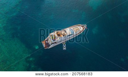 Aerial view of luxury motor yacht anchoring on coral reef. Bird eye view, water sport and relax