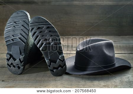 Rubber boots and felt hat on a wooden table