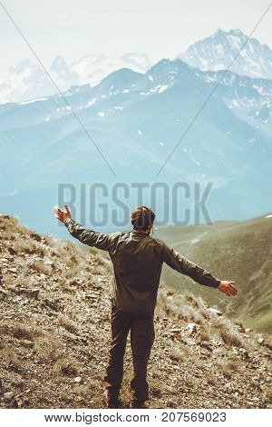 Happy Man walking at mountains landscape raised hands Travel Lifestyle wanderlust adventure concept summer vacations outdoor alone into the wild