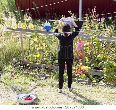 girl hanging clothes on a rope in nature .