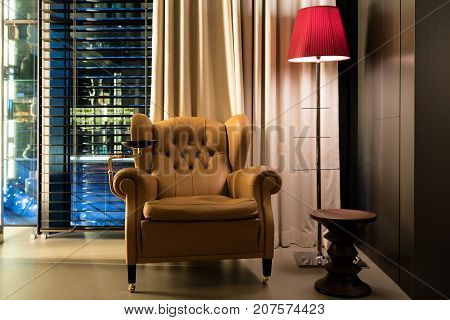 Leather armchair coffee table and floor lamp in lobby at hotel. Interior design of classic leather chair and lamp in dim room.